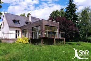 Extension maison ossature bois. Agrandissement d'habitat avec pose de baies vitrées, aménagement intérieur contemporain.